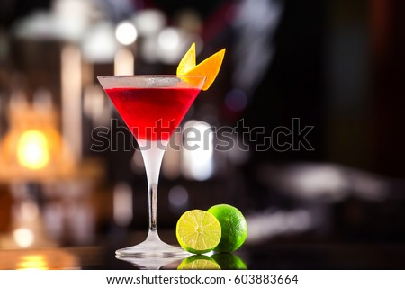 Closeup glass of cosmopolitan cocktail decorated with orange at bar background. #603883664