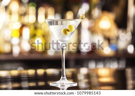 Closeup glass of martini dry cocktail with olives at bar counter background. #1079985143