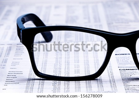 closeup glasses on financial newspaper under light tint blue