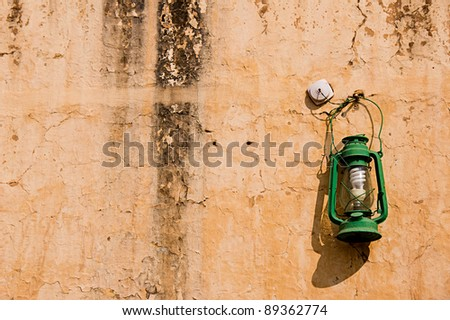 Closeup Green oil lamp hanging against ancient wall