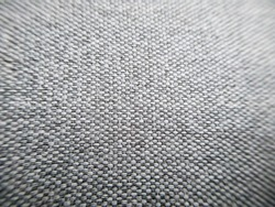 Closeup grey fabric texture with copy space. Macro shot of gray upholstery for furniture. Selective focus of gray textured fabric. Wallpaper and background. Thick gray material for the interior.