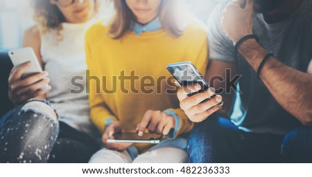 Closeup Group Adult Hipsters Friends Sitting Sofa Using Hands Modern Smartphone Tablet.Business Startup Friendship Teamwork Concept.People Working Together Project.Coworking Process Studio.Blurred