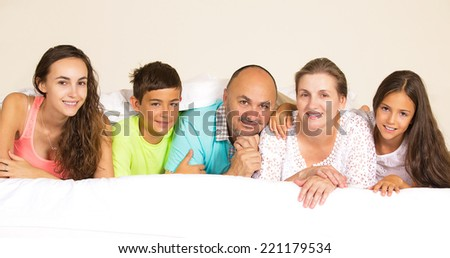 Closeup group portrait happy family, mother, father, children posing under duvet, blanket looking at camera on the bed at home, isolated room background. Positive emotions, face expressions, feelings