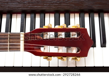 Closeup guitar neck on piano keys. Abstract and art background.