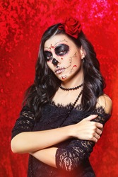 Closeup halloween style portrait of beautiful woman with facial art - traditional mexican skull at red background.