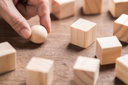 Closeup hand and wood sphere, try to find the right position to place it down among the cutting wood cubes, position in the market, business concept