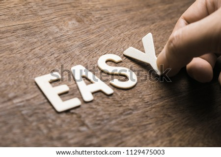 Closeup hand arrange wood letters as EASY word