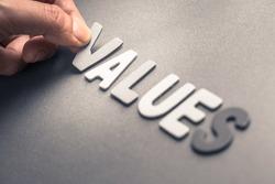 Closeup hand arrange wood letters as Values word