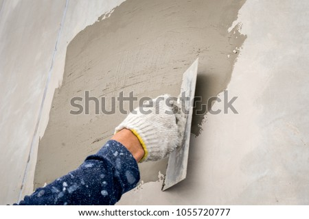 closeup hand construction plastering wet cement on the loft wall #1055720777