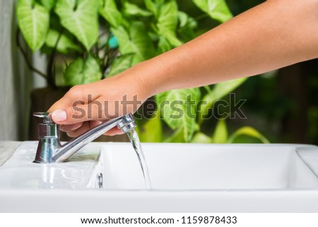 Closeup hand going to turn off the tap on washing basin with green plant on background