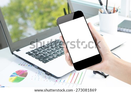 closeup hand hold smartphone and laptop on desk background community device in office