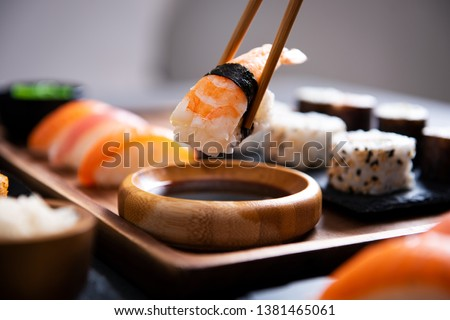 Closeup hand holding bamboo chopsticks with nigiri shrimp while soaking it in soy sauce. Detail of sushi set on wooden tray at restaurant while hand dip nigiri in soy sauce. Japanese cuisine concept.