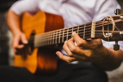 closeup hand musician playing acoustic guitar.concept for live music background,Music festival.Instrument on stage