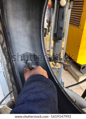 closeup hand of a repairman fixing a car tyre