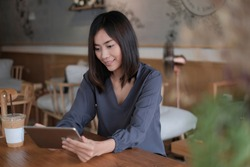 Closeup hand of Asian woman using ipad smartphone and touching screen in coffee shop, She smile reading good news on mobile phone , Business investment masking Lifestyle concept