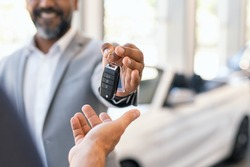 Closeup hand of cardealer giving new car key to customer. Salesman hand giving keys to a client at showroom. Man's hand receiving car keys from african agent in a auto dealership with copy space.
