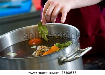 closeup hand of chef adding an aromatic bay leaf into pot with boiling vegetables