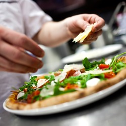 Closeup hand of chef baker in white uniform making pizza at kitchen