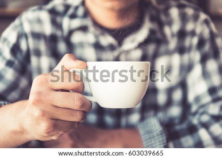 Stock Photo Closeup hand of male holding a coffee cup in the cafe add the filter retro color tone., How to lifestyle of adult businessman in the weekend activity relaxing with the coffee drinking concept.