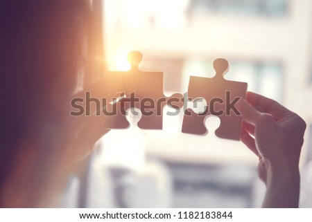 Closeup hand of woman connecting jigsaw puzzle with sunlight effect, Business solutions, success and strategy concept #1182183844