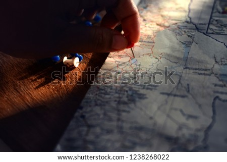 Closeup hand putting red pin to destination with East Asian map on wooden table.  #1238268022