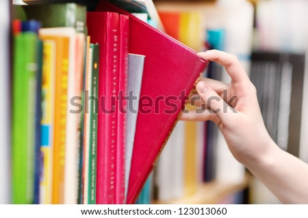 closeup  hand selecting book from a bookshelf