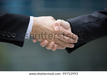 Closeup hand shake between two business man and woman.