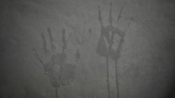 Closeup - Hand shapes against dark and opaque walls The hand shapes are paired with water drops on the wall with background lighting.