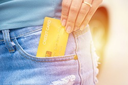 Closeup hand takes out generic of credit card in jeans trouser pocket
