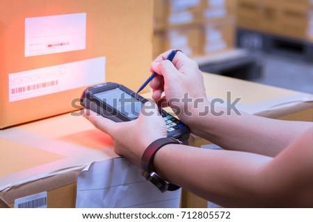 Closeup handheld scanning barcode on a box.