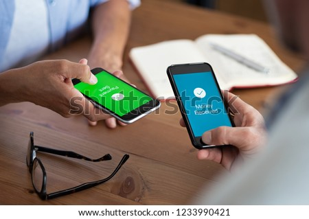 Closeup hands holding mobile phone with application for send and receive money. Man and woman holding smartphone and making payment transaction. Smart phone screen displaying payment sent.