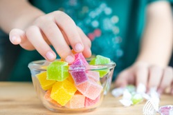 Closeup hands of a little child taking a piece of jelly cube with sugar in a glass bowl. Snacks time, Sugary treats, Party, Kids favorite, Unhealthy, Cavity, Sugar addiction, Sweetness, ADHD, Drug.