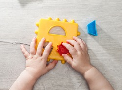 Closeup: Hands of a little Montessori kid learning about size, orders, sorting, arranging by engaged colorful wooden sensorial blocks. Educational toys, Cognitive skills, Montessori activity.