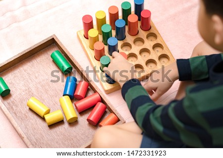 Closeup: Hands of a little Montessori kid (3-6) learning about size, orders, sorting, arranging by engaged colorful wooden sensorial blocks. Educational toys, Cognitive skills, Montessori activity. ストックフォト ©