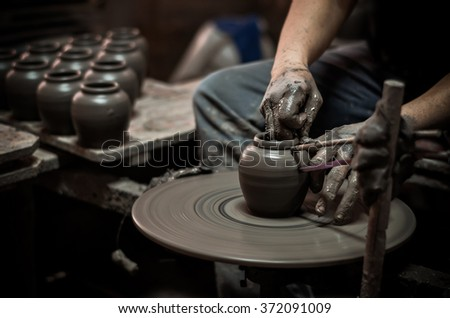 closeup hands of a potter, creating an earthen jar on the traditional machine, low light #372091009