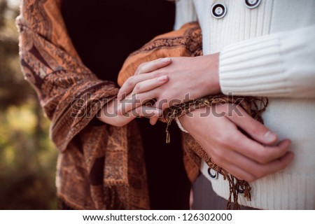 closeup hands of happy young couple in love outdoor in autumn