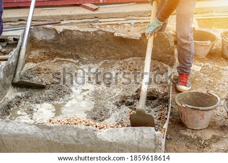 Closeup hands of laborer holding wood trowel working at construction site with sun flare background. Stock fotó ©