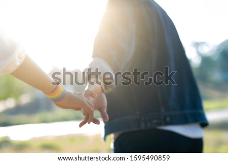 Closeup hands of LGBT lesbian couple. Couple of LGBT holding hands walking in the park. LGBT right concept.