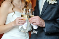 closeup hands of the bride and groom with glasses of champagne
