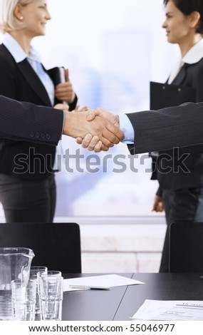 Closeup handshake in focus, businesswomen smiling in background in meeting room.