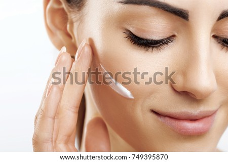 Closeup happy young woman applying cream to her face Skincare and cosmetics concept. Cosmetics. Woman face skin care.Natural makeup, touching face.