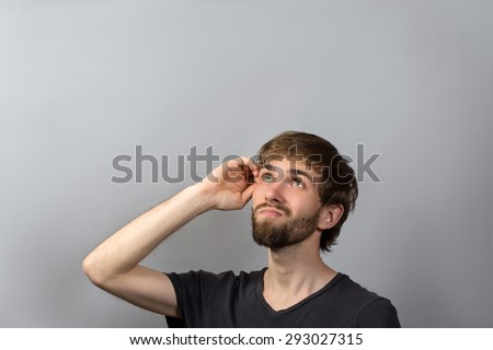 Closeup head shot undecided senior man scratching head thinking looking up isolated gray wall background with copy space