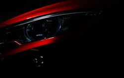Closeup headlight of shiny red luxury SUV compact car. Elegant electric car technology and business concept. Hybrid auto and automotive concept. Car parked in showroom or motor show. Car dealership.