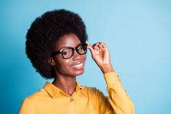 Closeup headshot photo of black skin extensive hairdo woman hold eyeglasses beaming shiny smile helping costumer buy optics wear specs yellow shirt isolated blue color background