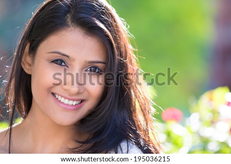 Closeup headshot portrait of confident smiling happy pretty young woman, isolated background of blurred trees, flowers. Positive human emotion facial expression feelings, attitude, perception