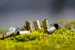 closeup heap of ammo shells in grass, military scene