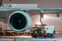 Closeup high detailed view of refueling operation of large widebody passenger aircraft standing on airport's parking place at ground maintenance at night