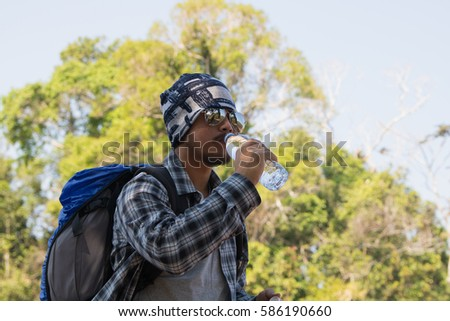 closeup Hiker drinking water. Happy man tourist with backpack dr #586190660