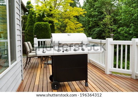 Closeup horizontal photo of BBQ grill on open cedar patio with seasonal trees in full bloom in background  #196364312