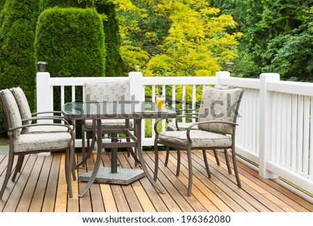 Closeup horizontal photo of outdoor furniture on open cedar patio with seasonal trees in full bloom in background